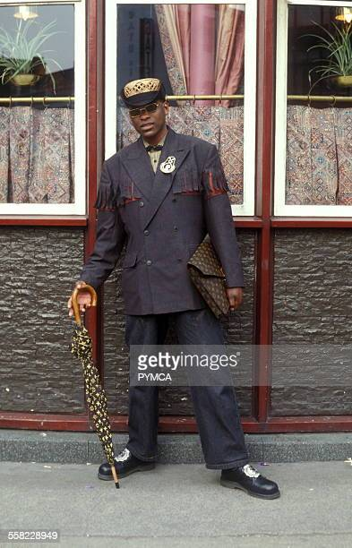 A man posing with an umbrella and bag wearing a grey suit Portobello Road London UK 1990s