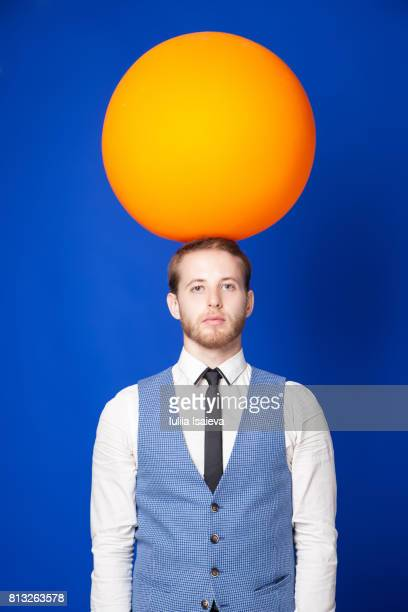 Man posing with ball on head