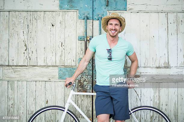 man posing with bicycle - white hat fashion item stock photos and pictures