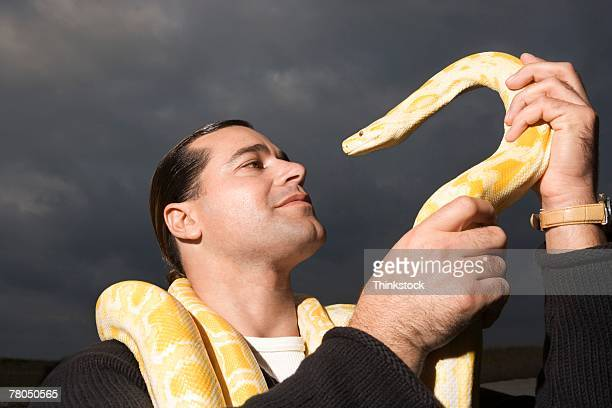 man posing with snake outdoors in miami - burmese python stock pictures, royalty-free photos & images