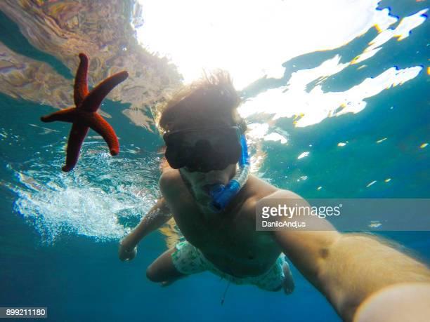 hombre posando con estrellas de mar bajo el agua