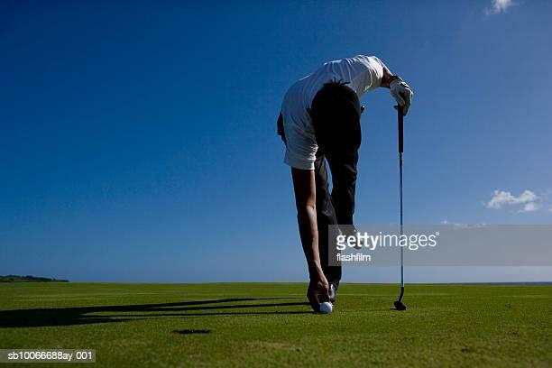 男性のポジショニングのゴルフコース、ゴルフボール