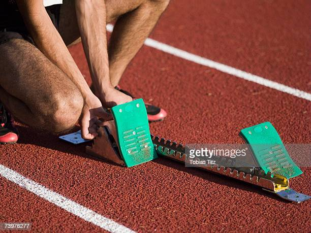 Man positioning starting blocks on a running track