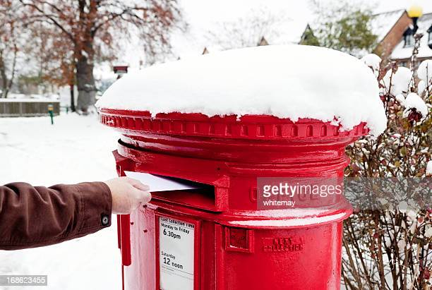 Man posting letter in snow-covered British postbox