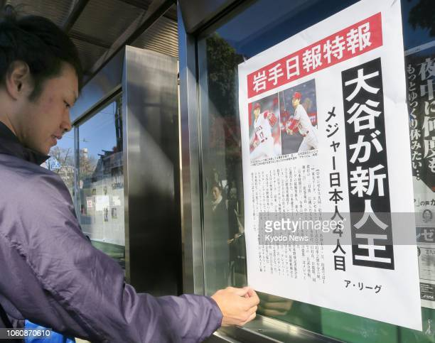 A man posts a copy of an extra edition of the Iwate Nippo newspaper in Morioka northeastern Japan on Nov 13 reporting that Shohei Ohtani of the Los...