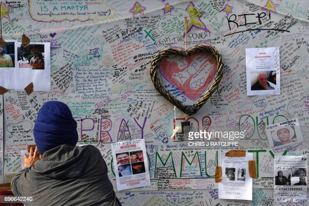 A man posts a picture of a missing person on a wall near the Grenfell Tower a residential tower block in west London which was gutted by fire on June...