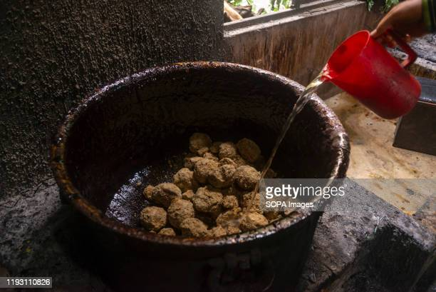 A man pour water in vessel containing molasses to boil raw hard molasses to make chaku for the Maghe Sankranti festival Chaku Molasses is usually...