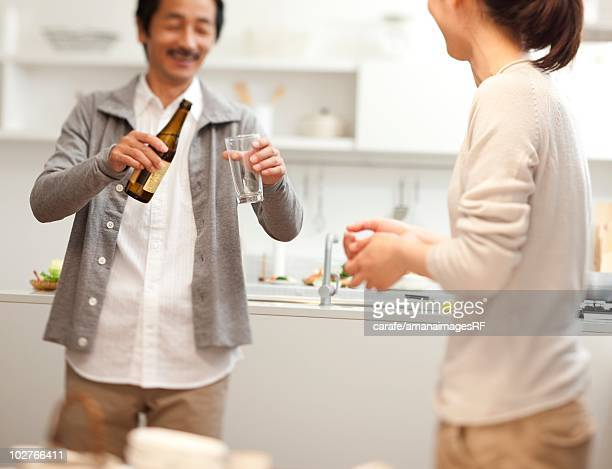 Man pouring a beer and talking to his daughter