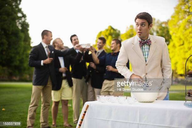 Man pouring alcohol into punch bowl