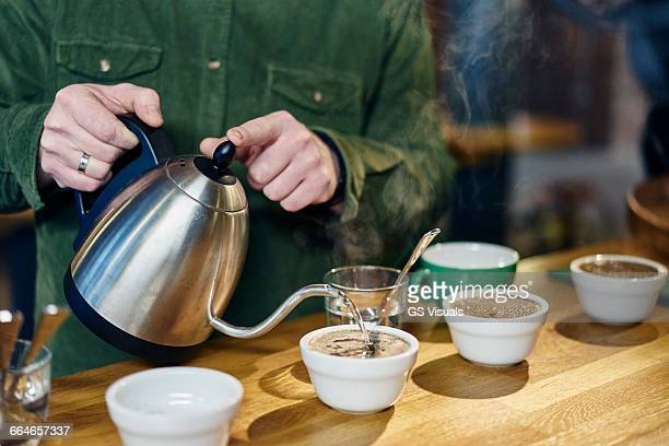 man pouring boiling water into coffee bowls for tasting on coffee shop counter - やかん ストックフォトと画像