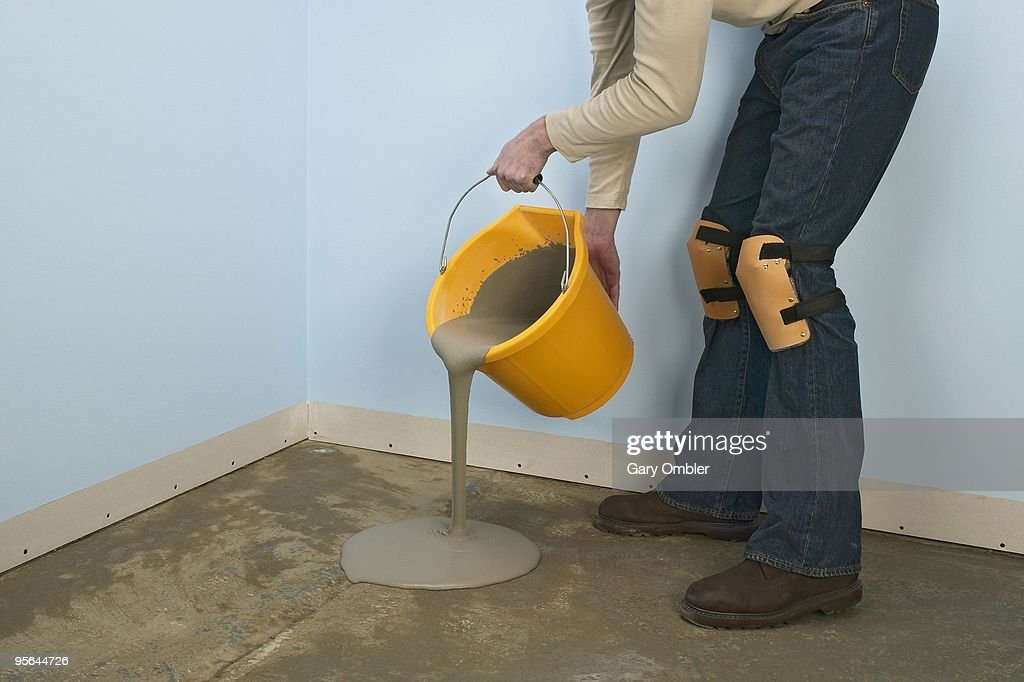 Man pouring bucket of self levelling compound on floor from bucket : Stock Photo