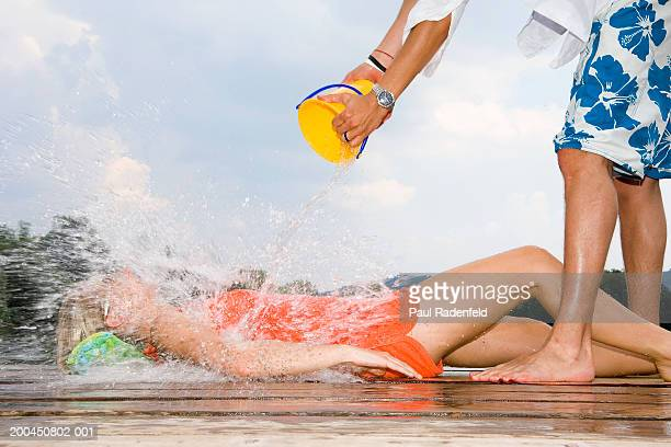 man pouring bucket of water over young woman lying down, side view - sezione inferiore foto e immagini stock