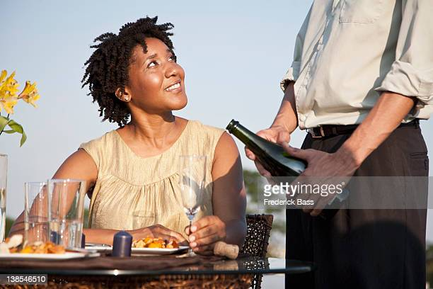 A man pouring champagne for a woman on a rooftop terrace