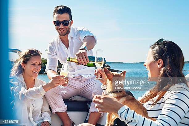 Man pouring champagne for young women on boat, Gavle, Sweden