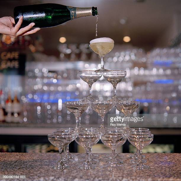 Man pouring champagne into pyramid of glasses in bar
