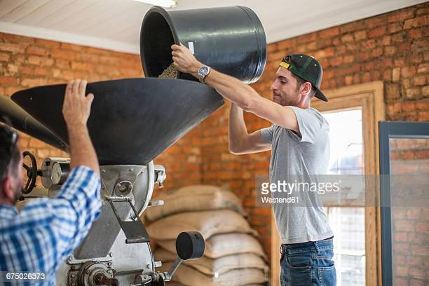 Man pouring coffee beans into a roasting machine