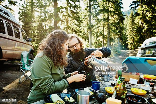 Man pouring coffee for wife while camping
