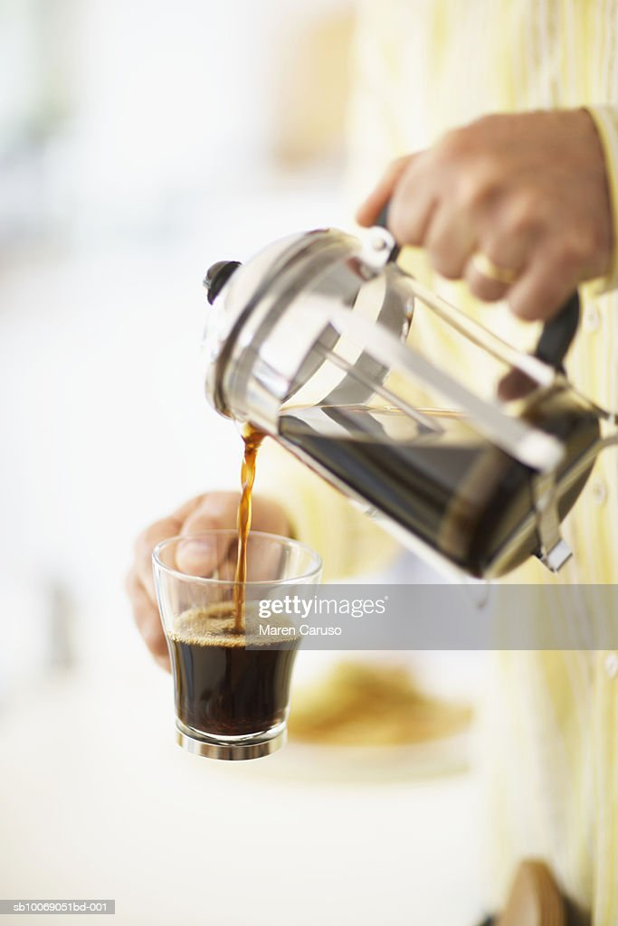 Man pouring coffee from cafetiere in to mug, close-up, mid section : Stockfoto