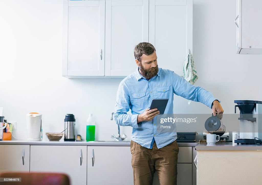 Man pouring coffee in cup at kitchen : Stock Photo