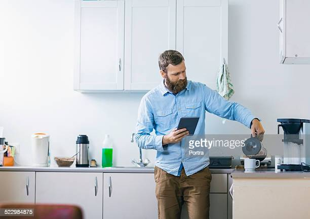 man pouring coffee in cup at kitchen - coffee maker stock pictures, royalty-free photos & images