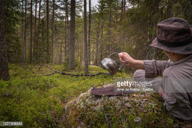 man pouring coffee into a wooden cup while resting in a forest - arne jw kolstø stock pictures, royalty-free photos & images