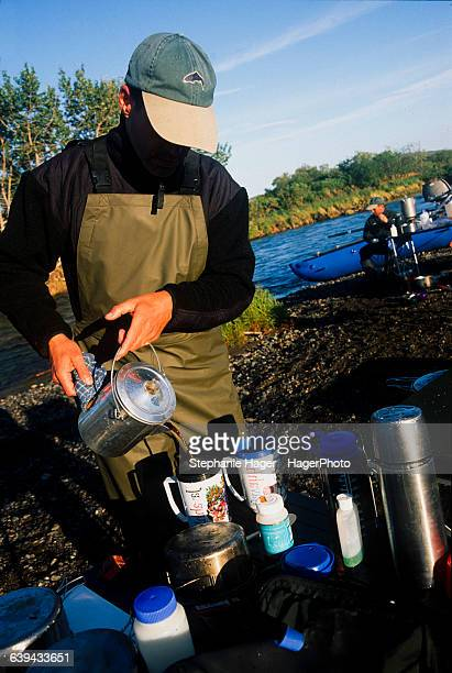 Man pouring coffee while camping