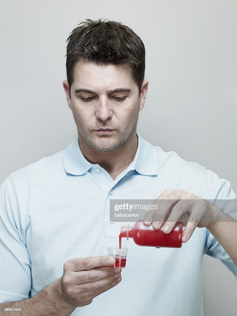 Man Pouring Cough Medicine into Measuring Cup. : Stock Photo