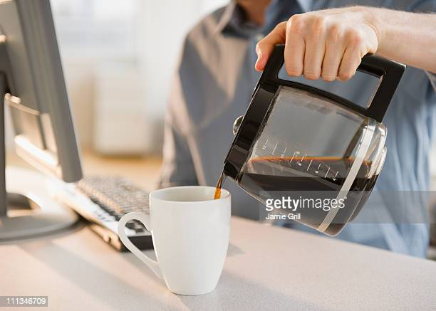 Man pouring cup of coffee, close-up