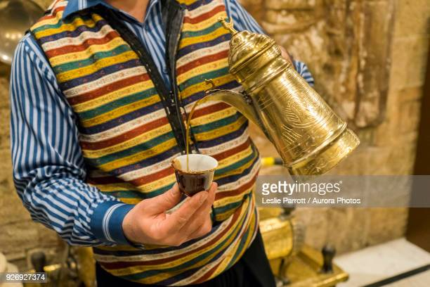 man pouring cup of traditional arabic tea from dallah, amman, jordan - jordanian stock pictures, royalty-free photos & images