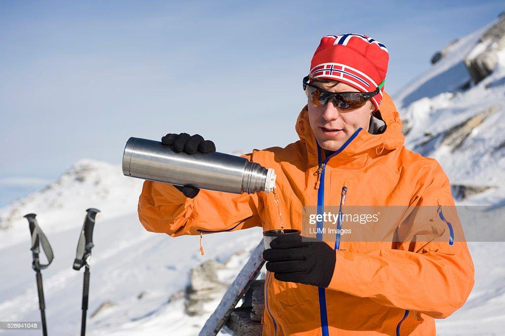Man pouring from vacuum flask in mountain landscape, Weissenseegletscher, Salzburg, Austria : Stockfoto