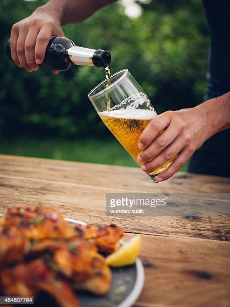 Man pouring glass of beer with chicken wings in foreground