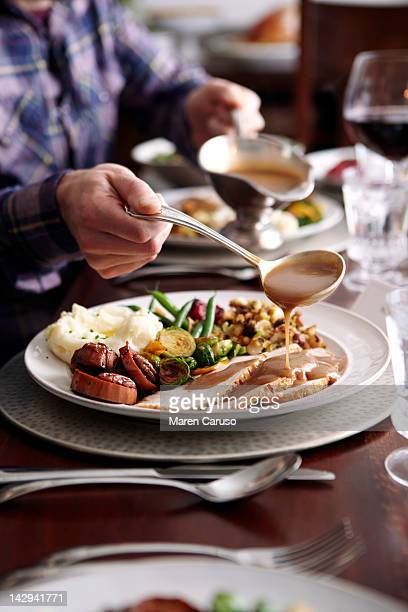 man pouring gravy onto turkey meal - free thanksgiving stock pictures, royalty-free photos & images