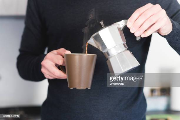 Man pouring hot espresso in a mug, partial view