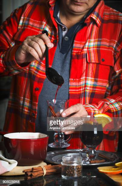 Man pouring hot mulled wine in glass cup