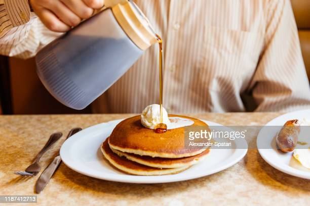 man pouring maple syrup over pancakes in the diner - pancake stock pictures, royalty-free photos & images