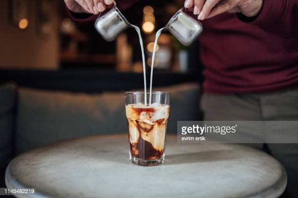 man pouring milk in iced coffee - mixing stock pictures, royalty-free photos & images