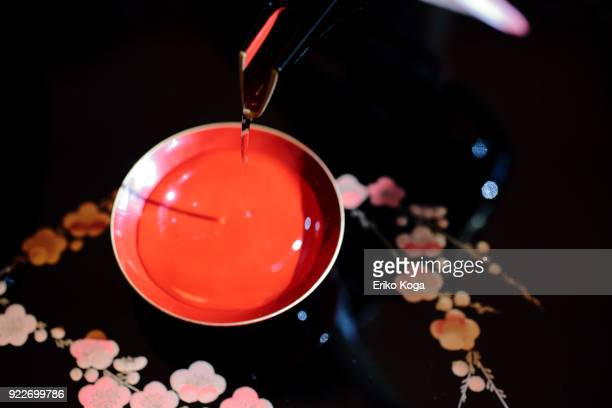 man pouring new year's spiced sake called otoso - new year's day stock pictures, royalty-free photos & images