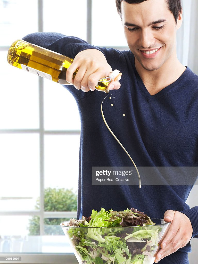 Man Pouring Olive Oil On To Fresh Green Salad High-Res ...