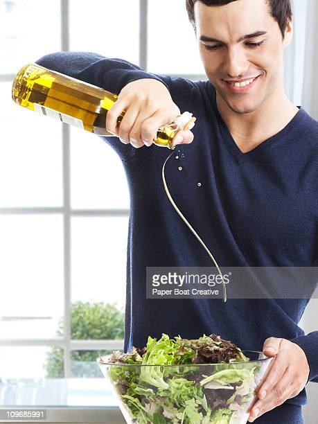 Man pouring olive oil on to fresh green salad
