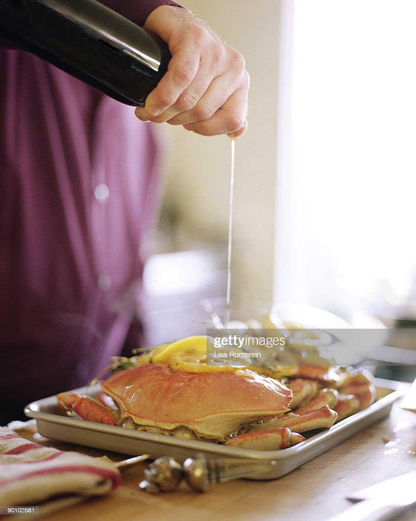Man pouring olive oil on whole dungeness crabs : Stock Photo