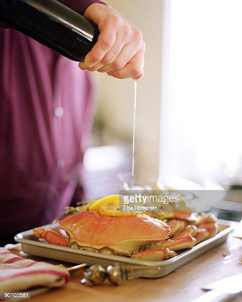 Man pouring olive oil on whole dungeness crabs
