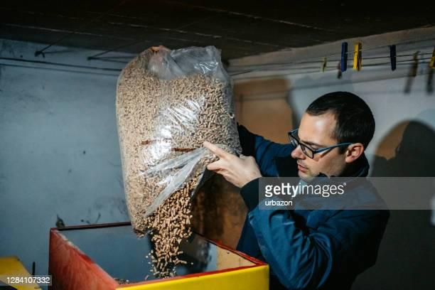 man pouring pellets in pellets boiler - grânulo imagens e fotografias de stock