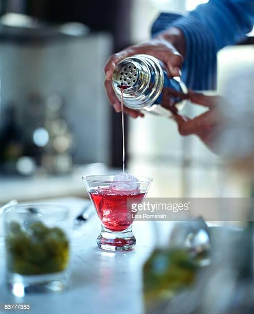 Man pouring pomegranate martini