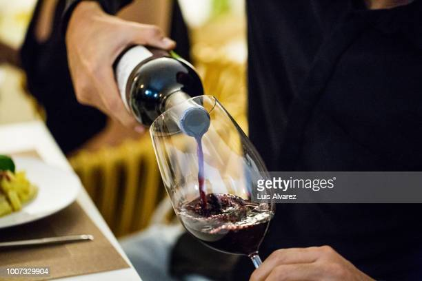 man pouring red wine in glass during dinner party - copa de vino fotografías e imágenes de stock