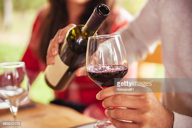 Man pouring red wine into glass