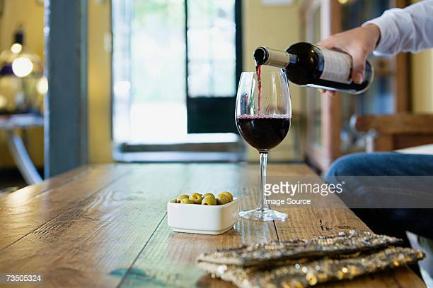 man pouring red wine - green olive stock photos and pictures