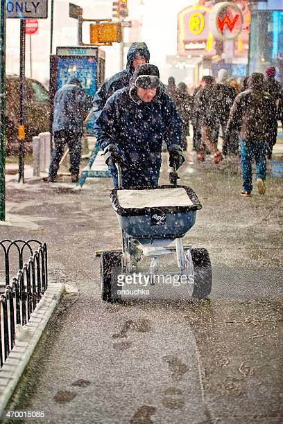 man pouring salt on new york streets during snow blizzard - road salt stock pictures, royalty-free photos & images