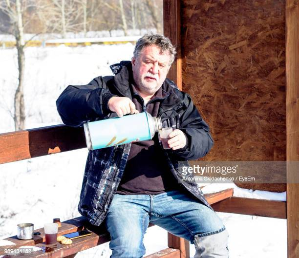 Man Pouring Tea While Sitting On Bench During Winter