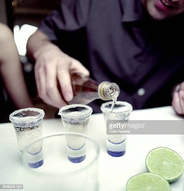 Man pouring tequila into glass, close-up