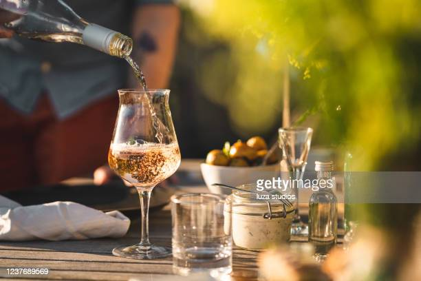 man pouring up rose wine at midsummer dinner - national holiday stock pictures, royalty-free photos & images